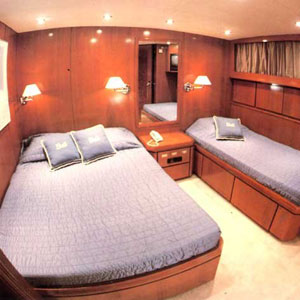 yacht stateroom with wooded panel, queen bed and bunk
